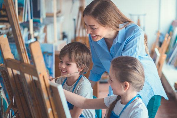 Kvinde og børn har det hyggeligt med at male i fælleshusets atelier